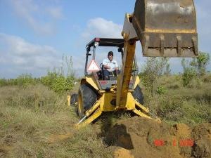 Employee Using a Back Hoe to Dig