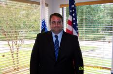 City Manager Inside an Office Standing in Front of Windows and Flags