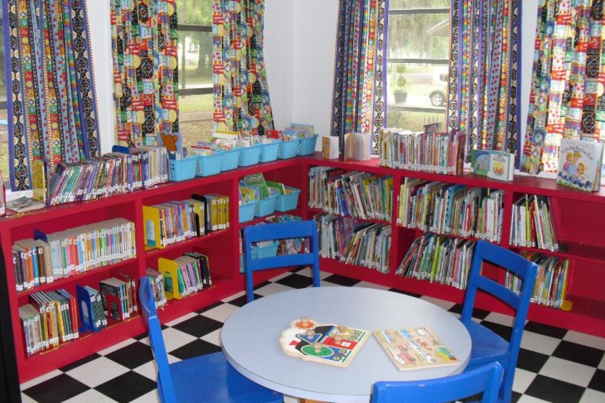 Children's Reading Room - corner of room with low shelves full of childrens' books - small round table in front
