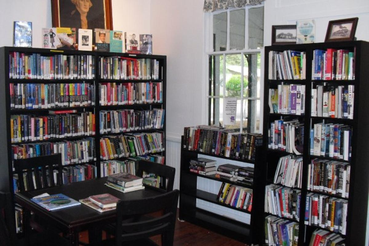 Interior of the Schoolhouse Library - bookshelves at corner of building, full of books - a small window in wall on right