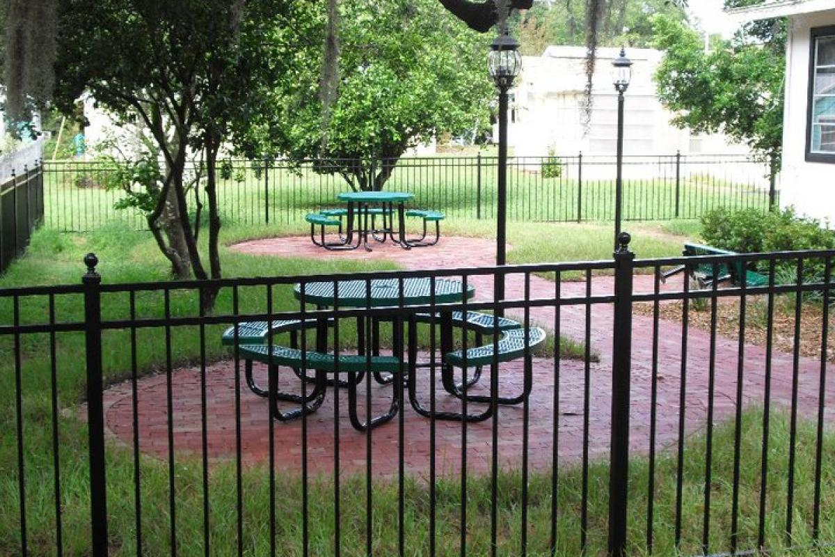 Schoolhouse Library Garden - round outdoor table on patio surrounded by wrought iron fence